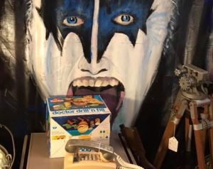 Painting of Gene Simmons behind a Drill N Fill dentist game