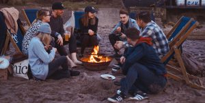 Group of young adults sitting around a firepit talking